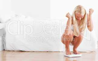 Cheerful woman squatting on a weighing machine