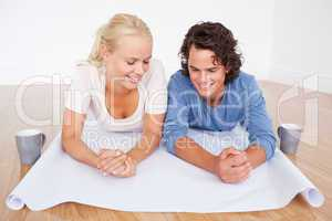 Close up of a couple looking at a plan with cups of coffee