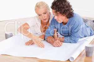 Couple looking at their future room on a plan