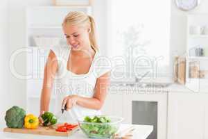 Blond-haired woman slicing pepper