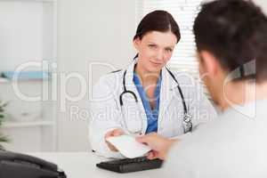 Female doctor giving patient a prescription