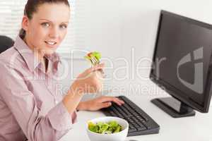 Businesswoman in office eating salad