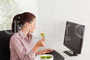 Businesswoman eating salad whilst looking to screen