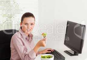 Businesswoman eats salad