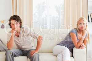 Upset couple sitting on a sofa
