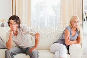Sorrowful couple sitting on a couch