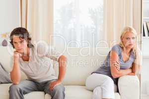 Sorrowful couple sitting on a sofa