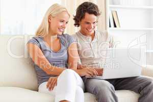 Smiling in love couple using a laptop