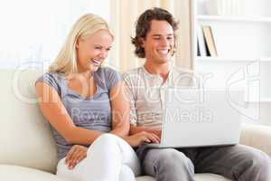 Couple having fun while using a laptop
