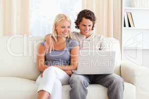 Friendly couple using a laptop