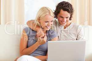 Smiling young couple using a laptop