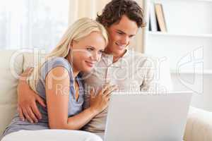 Lovely young couple using a notebook