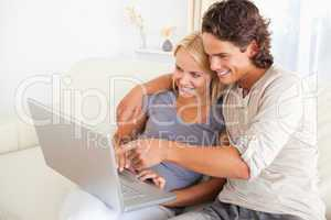 Man showing something to his wife on a screen