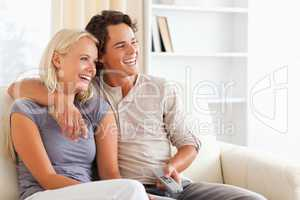 Laughing couple watching TV