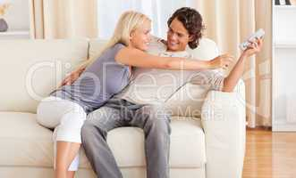 Happy couple fighting for the remote
