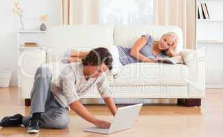 Man using a laptop while his girlfriend is holding a book