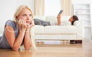 Woman lying on the floor while her fiance is reading a book