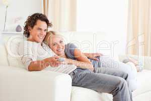 Couple cuddling while watching TV