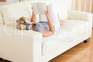 Woman listenning to music while reading a book