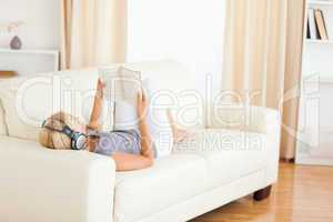 Woman enjoying some music while reading a book