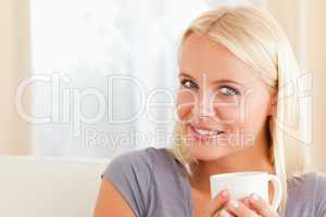 Close up of a woman sitting on a couch with a cup of coffee