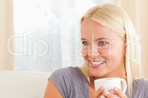 Close up of a woman sitting on a couch with a cup of tea