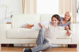 Laughing cute couple watching TV