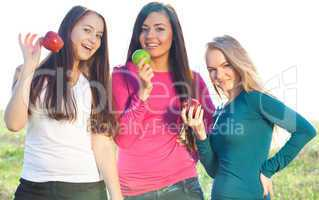 portret of three young beautiful woman with apple on the  sky ba