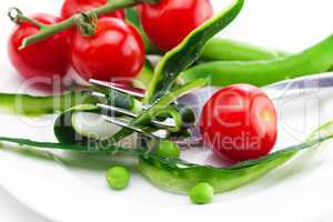 tomato,fork ,cucumber skin,peas and measure tape on a plate isol