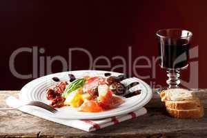 gemischte italienische Antipasti auf einem Teller mit Wein
