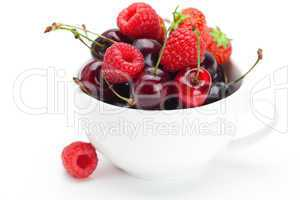 raspberries, strawberries and cherries in a bowl isolated on whi