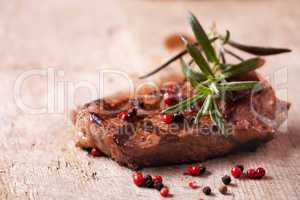 Nahaufnahme von einem Rosmarinzweig auf ein Steak