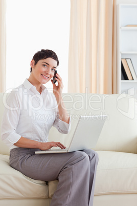 Cute Woman with a laptop and a phone looking into the camera