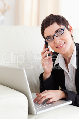 Businesswoman lying on a sofa with a laptop and a phone wearing