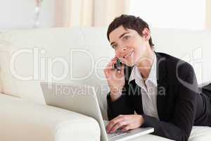 Charming Woman lying on a sofa with a laptop and a phone