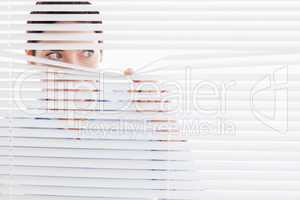 Curious businesswoman peeking out of a window
