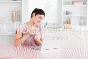 Cute Woman working with a laptop holding a cup