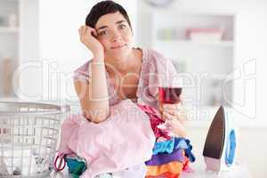 Sad Woman with wine and a pile of clothes