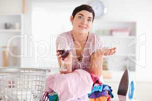Beautiful Woman with wine and a pile of clothes