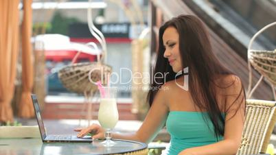 Young woman Using Laptop at Outdoor Cafe