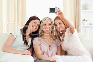 Cute women lounging on a sofa with a camera