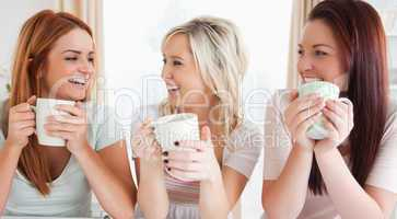 Young Women sitting at a table with cups
