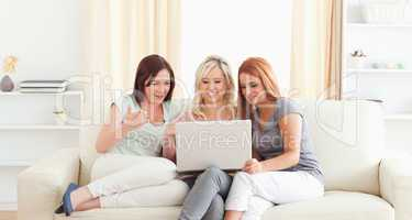 Young women relaxing on a sofa with a laptop