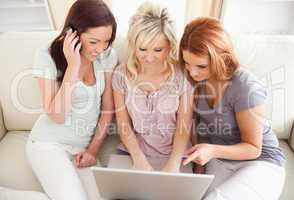 Freundinnen sitzen mit Handy und Laptop auf Couch