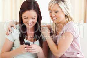 zwei Frauen sitzen mit Handy auf der Couch