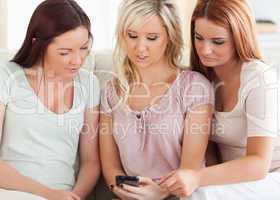 Freundinnen  sitzen mit Handy auf der Couch