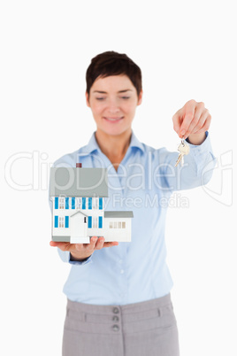 Real estate agent showing keys and a miniature house
