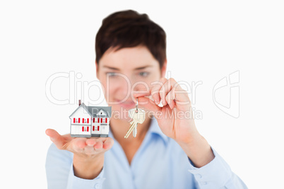 Close up of a businesswoman showing keys and a miniature house