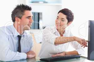 Office worker pointing a something on a screen to her colleague
