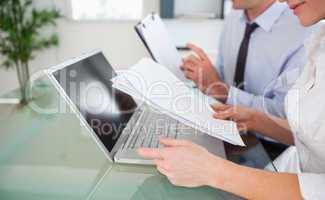 Managers typing a report from blueprint documents